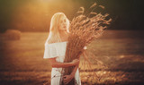 Beautiful blond in field at sunset looking away