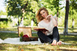 Young fashion woman reading a book in a city park