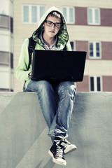 Young man with laptop sitting on the sidewalk
