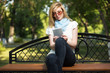 Young fashion woman using tablet computer in a city park