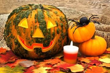 Spooky Halloween Jack o Lantern with autumn decor against wood