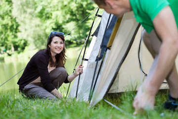 Woman and man pitching a tent