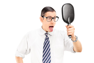 Man looking in mirror and sticking his tongue out