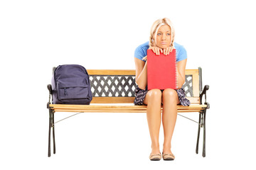 Sad female student sitting on a wooden bench
