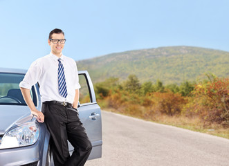 Young man standing by a car on an open road