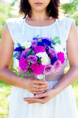 Bridesmaid holds a wedding bouquet of roses in purple tones. Flo