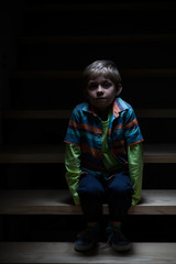 Boy alone on stairs at night