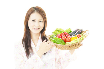 野菜を持つ笑顔の女性