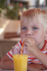 little boy with a orange juice