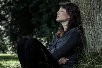 Sad woman sitting under the tree