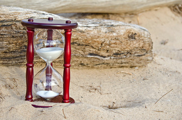 sand timer in sand with driftwood