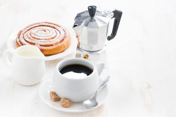 cup of black coffee, cream, sweet bun and coffeemaker