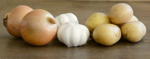 Close up of fresh onions, yellow potatoes, and garlic