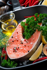 fresh salmon steak and ingredients for cooking on grill pan