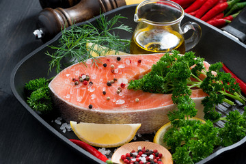 fresh salmon steak and ingredients for cooking on a grill pan