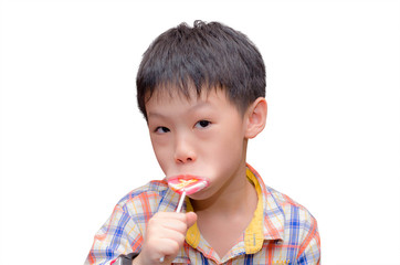 little Asian boy eating candy in his hand, isolated on a white b