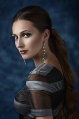 Beautiful elegant woman with evening make-up and long earrings.