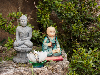 Buddhist novice monk dolls with Buddha image on the rock
