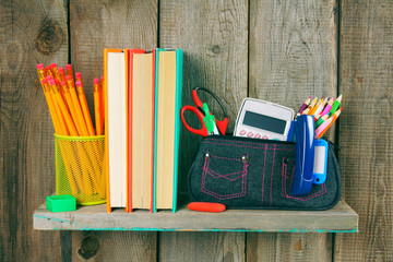 Books and school tools on a wooden shelf.