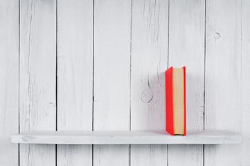 Book on a wooden shelf.