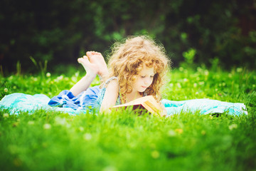 Little girl reading a book in the spring park, toning photo