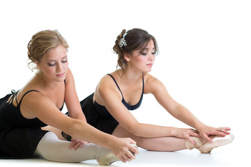 Two beautiful young girls making stretching exercise or splits t