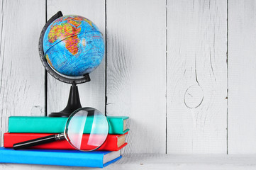 The globe, magnifier and books .