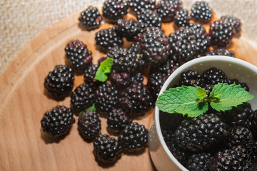 Blackberries with mint  in cup and wooden table
