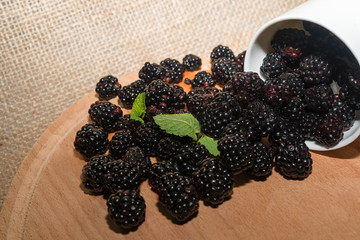 Blackberries with mint  in cup on a wooden table and matting