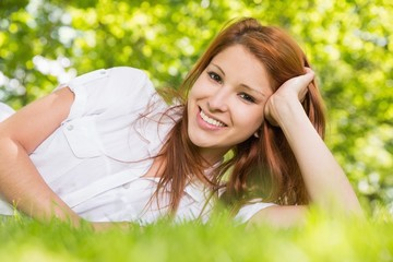 Pretty redhead lying on the grass smiling at camera