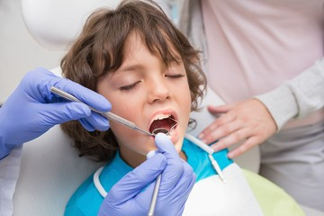 Pediatric dentist examining a little boys teeth with his mother