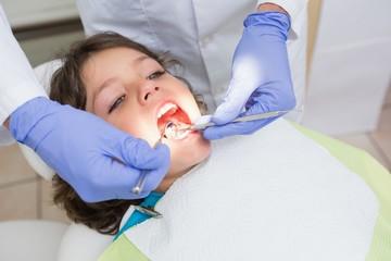 Pediatric dentist examining a boys teeth