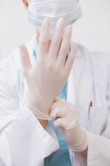 Dentist pulling on surgical gloves