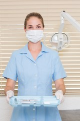 Dental assistant in mask holding tray of tools