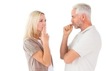 Couple staying silent with fingers on lips