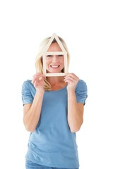 Happy blonde holding house outline over face