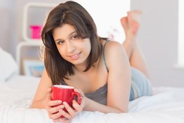 Beautiful brunette lying on bed holding mug