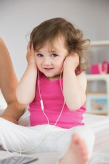 Cute little girl listening to music on bed