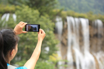young woman tourist taking photo with smart phone outdoor