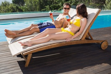 Couple with drinks sitting by swimming pool