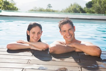 Smiling couple in swimming pool on a sunny day