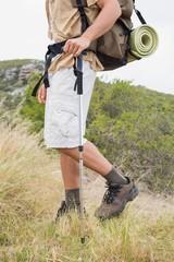 Low section of hiking man walking on mountain terrain