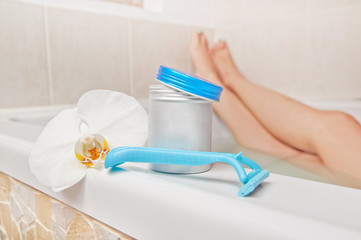 Epilation time - woman legs in bath and shaving accessories. Ski