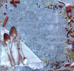 Old cutlery and variety spices ingredient on vintage board