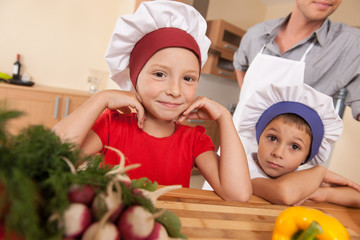 Portrait of parents and two children making food.