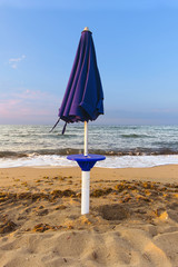 Abandoned beach with closed umbrella