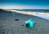 Pollution and waste on the beach in sunset light