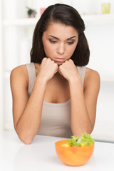 upset young woman keeping diet and eating vegetables.