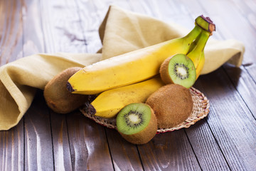Kiwi and bananas on wooden background