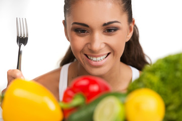 Girl with vegetables isolated on white background.